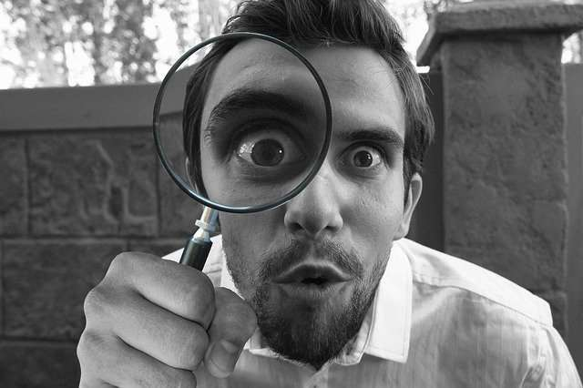A man with a magnifying glass searching for clues